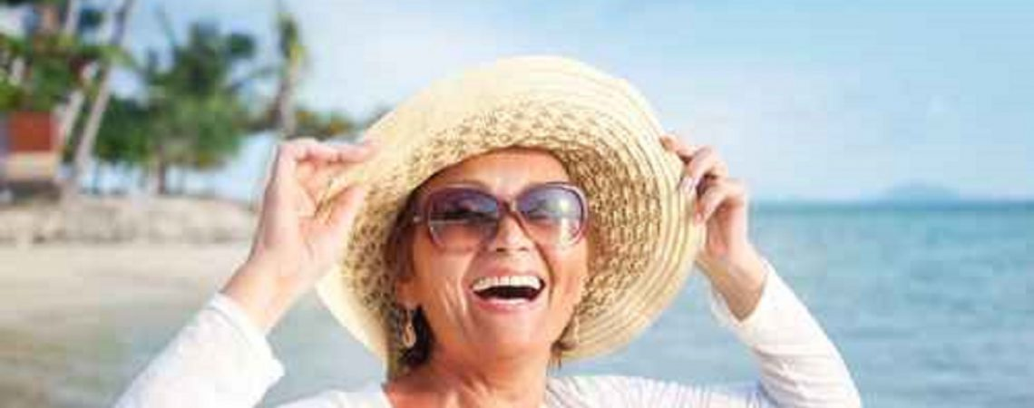 Happy senior woman on beach enjoying life with Medicare Advantage