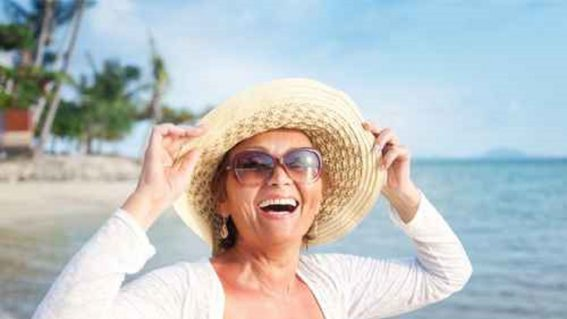 Happy senior woman on beach enjoying life with Medicare Advantage